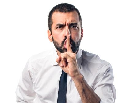 ? ?  ? �silence: Hombre de negocios haciendo el gesto de silencio Foto de archivo