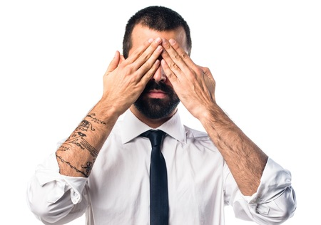 covering: Businessman covering his eyes
