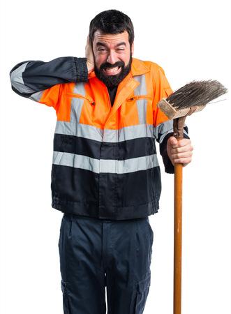 Garbage man covering his ears
