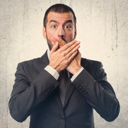 covering: Businessman covering his mouth Stock Photo