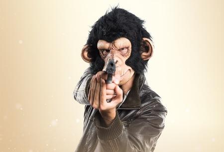 holding gun to head: Monkey man holding a pistol Stock Photo