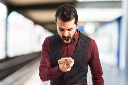 important phone call: Man wearing waistcoat shouting by mobile