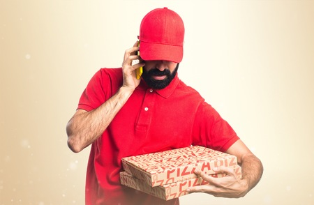 pizza delivery: Pizza delivery man talking to mobile Stock Photo
