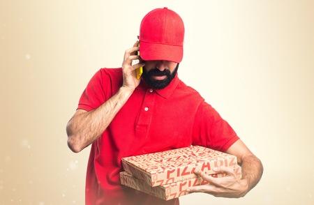 repartidor de pizzas a hablar con el móvil