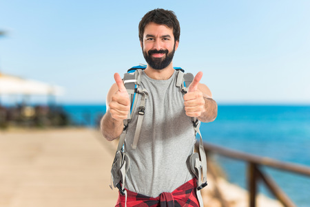 bonne aventure: Backpacker with thumb up sur fond blanc