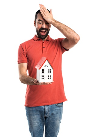 icone: Handsome man holding a little house Stock Photo