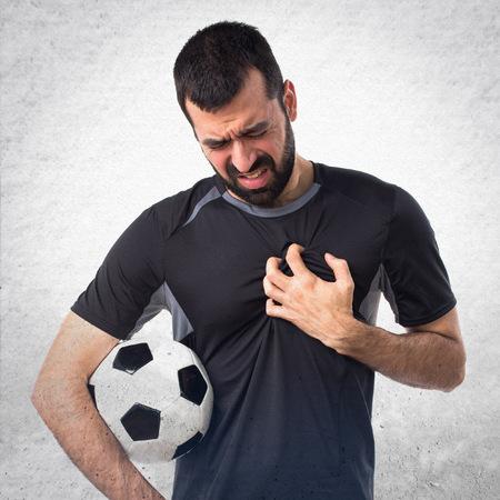 dolor de pecho: jugador de fútbol con dolor en el corazón Foto de archivo