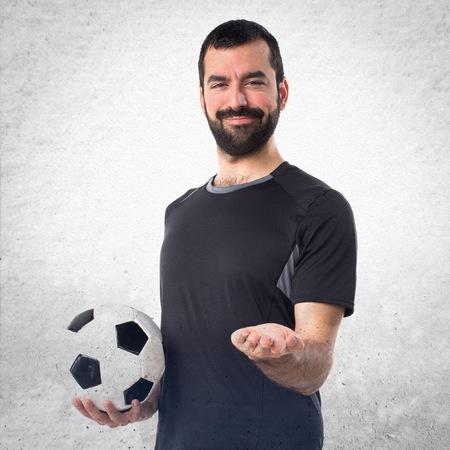 something athletic: Football player holding something