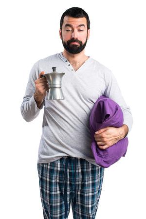 coffee pot: Man in pajamas holding a coffee pot