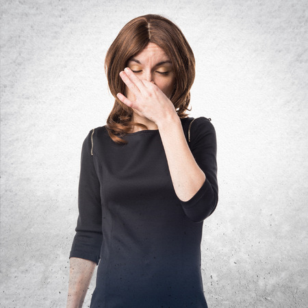 Brunette woman making smelling bad gesture