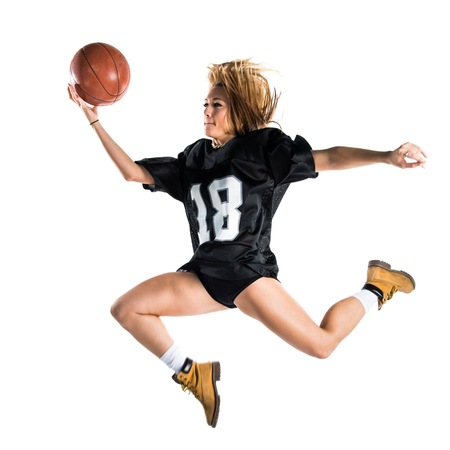 Woman jumping and playing basketball Stock Photo