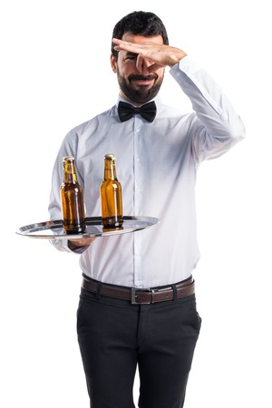 smell: Waiter with beer bottles on the tray making smelling bad gesture Stock Photo