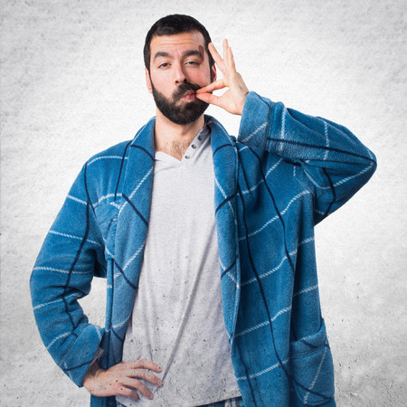 dressing gown: Man in dressing gown making silence gesture