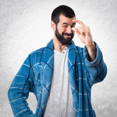 dressing gown: Man in dressing gown doing tiny sign Stock Photo
