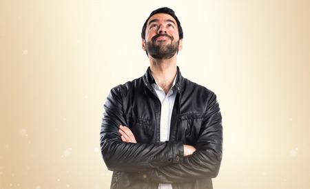 personas mirando: Hombre con la chaqueta de cuero que mira hacia arriba