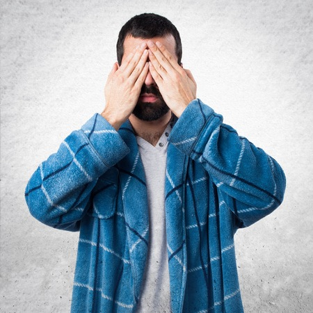 dressing gown: Man in dressing gown covering his eyes