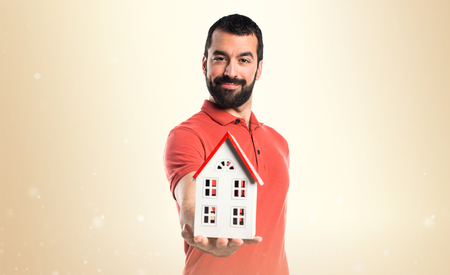 handsome: Handsome man holding a little house Stock Photo