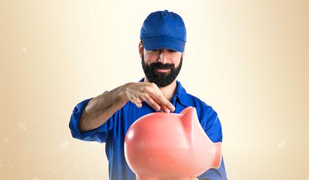 Plumber holding a piggybank