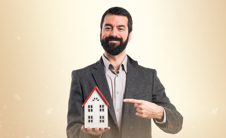 icone: Man holding a little house Stock Photo