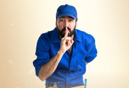silence gesture: Plumber making silence gesture