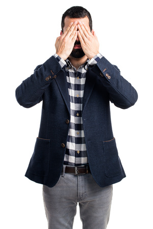 gesticulate: Handsome man covering his eyes