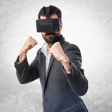hit tech: Man using VR glasses giving a punch