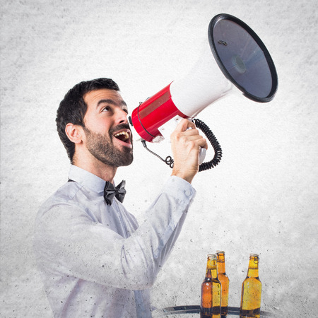 Waiter with beer bottles on the tray shouting by megaphone