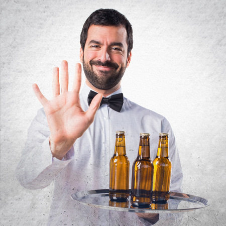 counting five: Waiter with beer bottles on the tray counting five Stock Photo