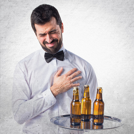 heartache: Waiter with beer bottles on the tray with heart pain