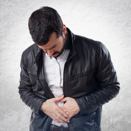 stomachache: Man with leather jacket with stomachache Stock Photo
