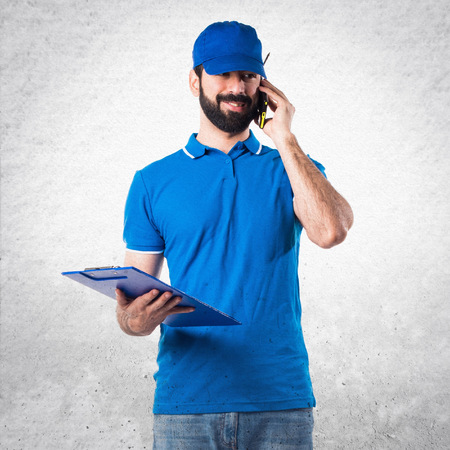 service man: Delivery man with folder talking to mobile