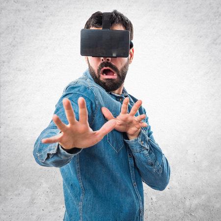 frightened: Frightened man using VR glasses