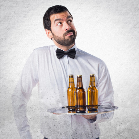 unimportant: Waiter with beer bottles on the tray making unimportant gesture