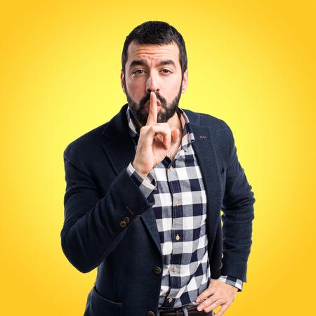 silence gesture: Handsome man making silence gesture