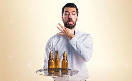 drowning: Waiter with beer bottles on the tray drowning himself Stock Photo