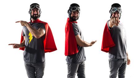 alzando la mano: Superhero presenting something Foto de archivo
