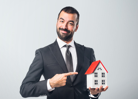 icone: Businessman holding a little house Stock Photo