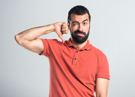 disapprove: Handsome man doing bad signal Stock Photo