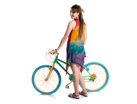 Girl with dreadlocks on colorful bike Stock Photo