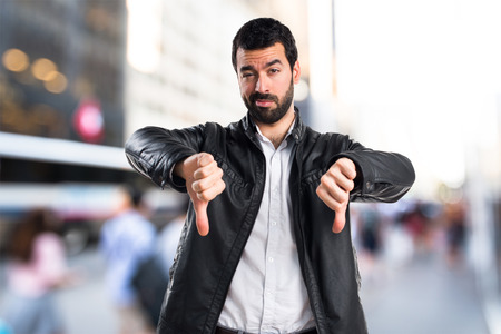 Man with leather jacket doing bad signal Stock Photo