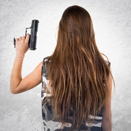 youth crime: Young girl holding a pistol