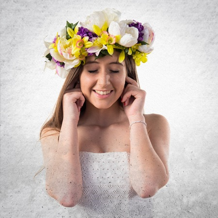 ignore: Girl with crown of flowers covering her ears