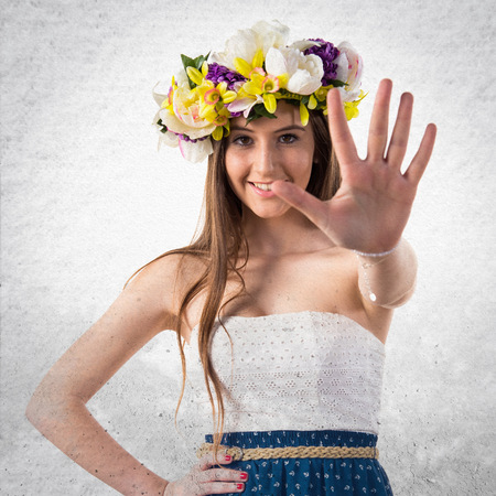 counting five: Girl with crown of flowers counting five Stock Photo