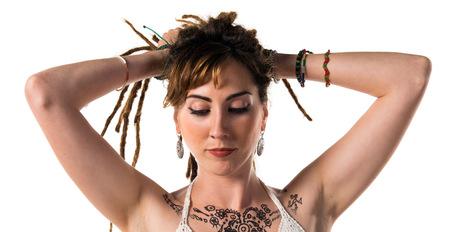rastas: Tattooed girl with dreadlocks posing in studio