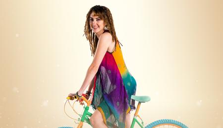 rasta colors: Girl with dreadlocks on colorful bike Stock Photo