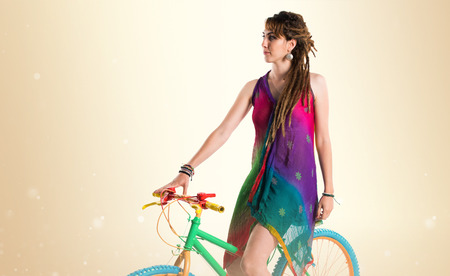 dreadlocks: Girl with dreadlocks on colorful bike Stock Photo