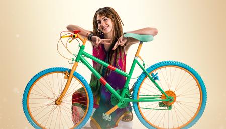 rastas: Girl with dreadlocks on colorful bike Foto de archivo