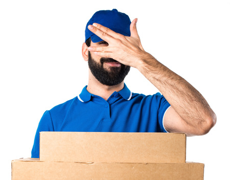 covering: Delivery man covering his face