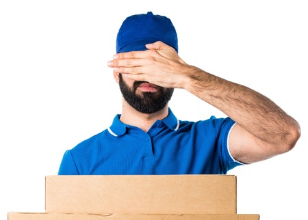covering: Delivery man covering his eyes Stock Photo