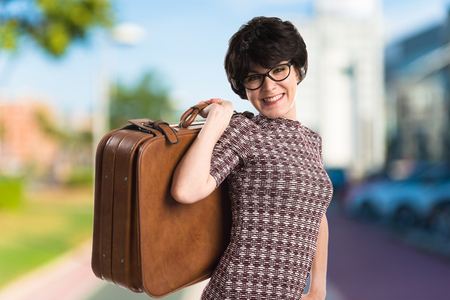 Girl with vintage look holding a suitcase